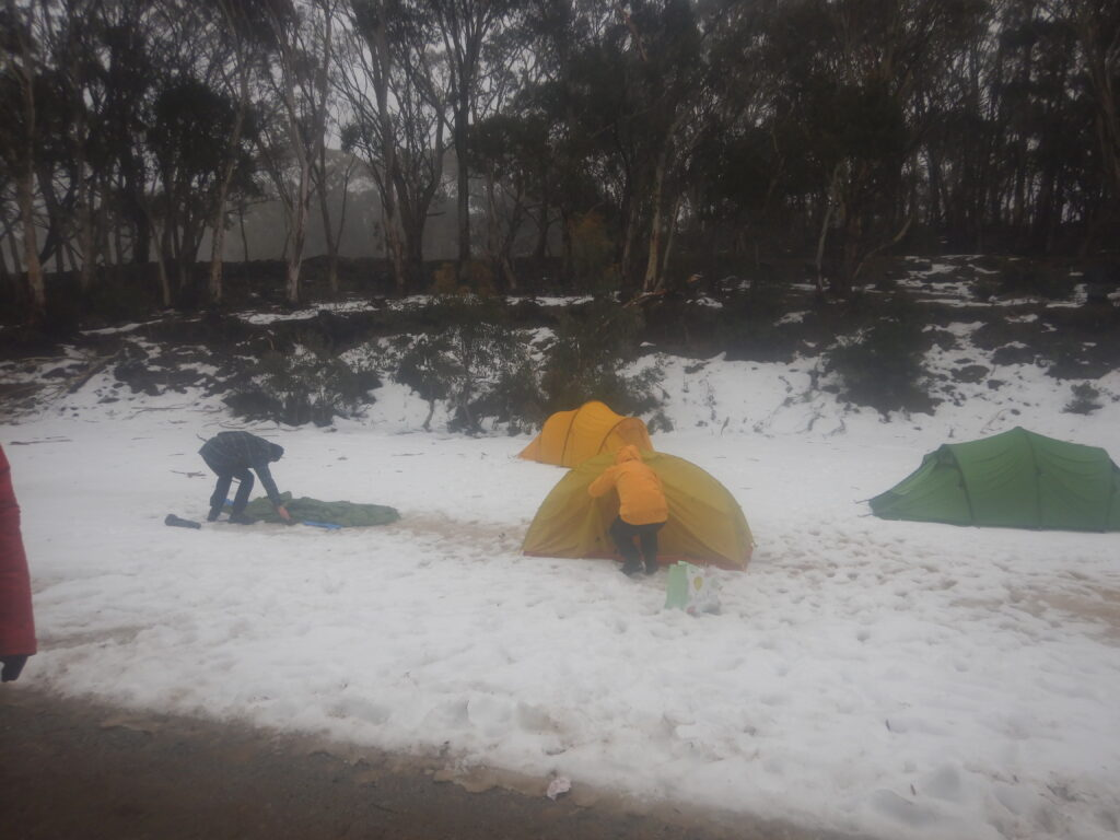 A Rover in a yellow hard shell jacket packs up a tent in the rain